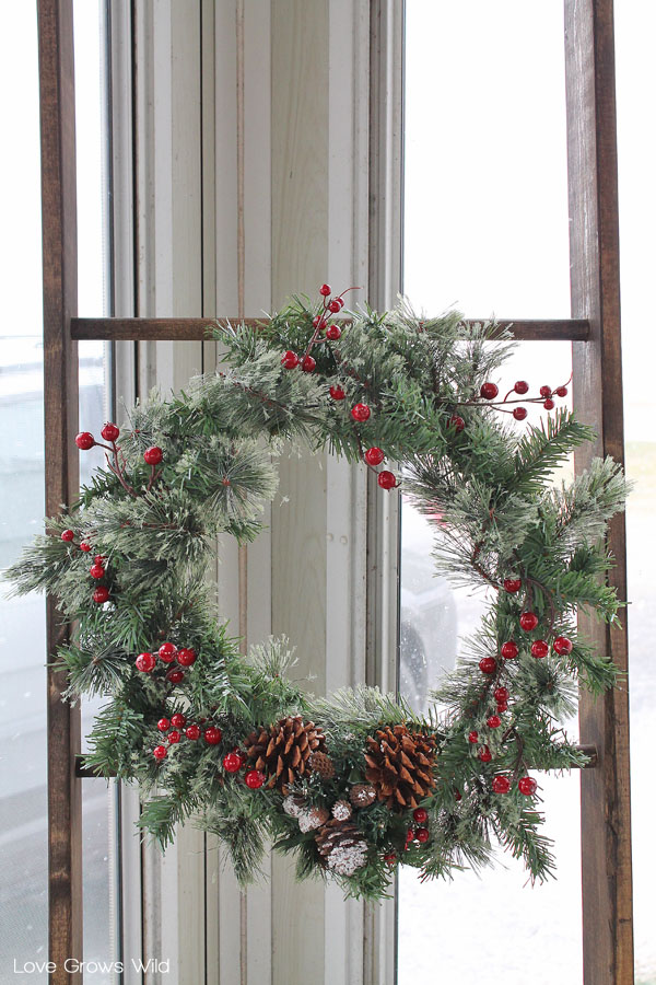 Use a rustic wood ladder to hang a winter wreath for the holidays.