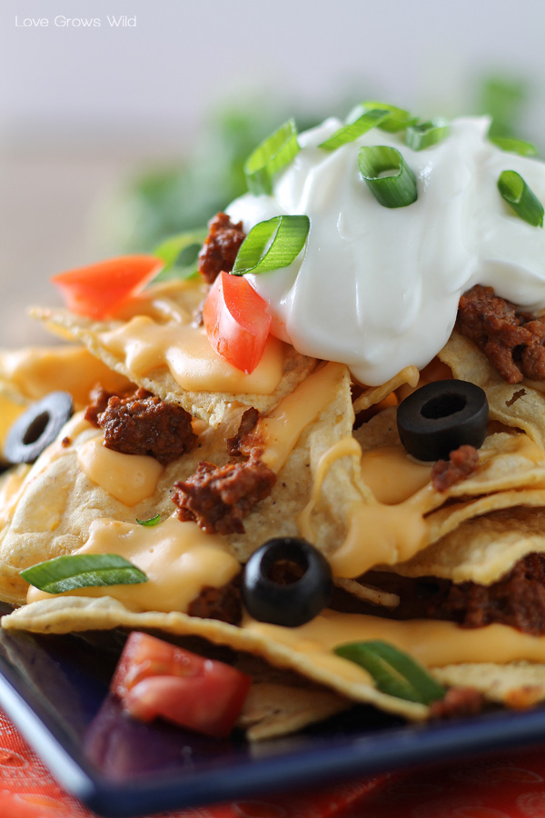Chili Cheese Nachos are the perfect party food, with layers of beefy chili, homemade cheese sauce, and piled high with tasty toppings!