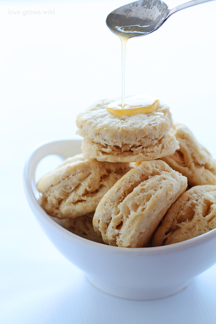 Tender, flaky biscuits made with coconut oil and topped with sweet honey butter! | LoveGrowsWild.com