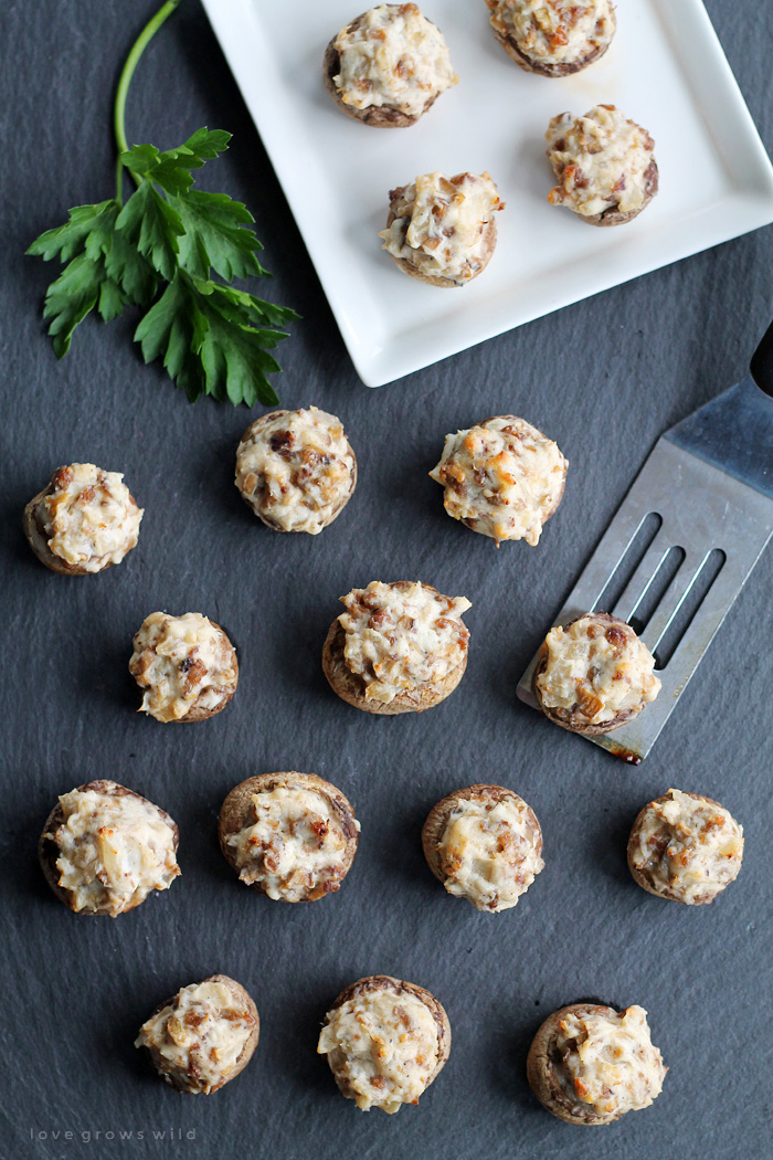Creamy, delicious Sausage Stuffed Mushrooms make the perfect party appetizer!  Get the recipe for these savory little bites of heaven at LoveGrowsWild.com