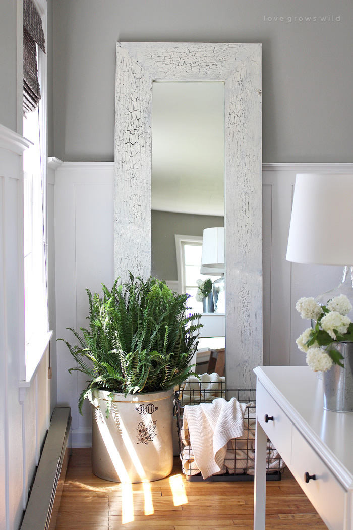 Turn a boring, basic mirror into a gorgeous wood framed floor mirror that will bounce light all throughout the room! Get the tutorial at LoveGrowsWild.com