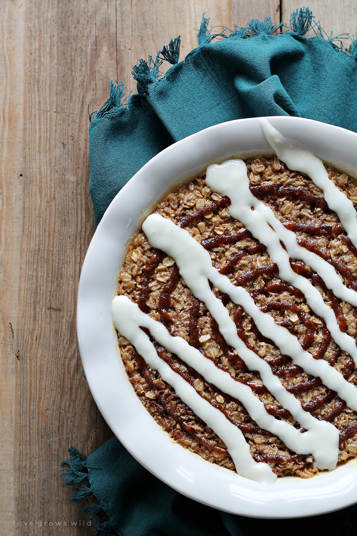 Delicious, easy baked oatmeal with a sweet cinnamon drizzle and cream cheese icing! Cinnamon roll perfection! Get the recipe at LoveGrowsWild.com