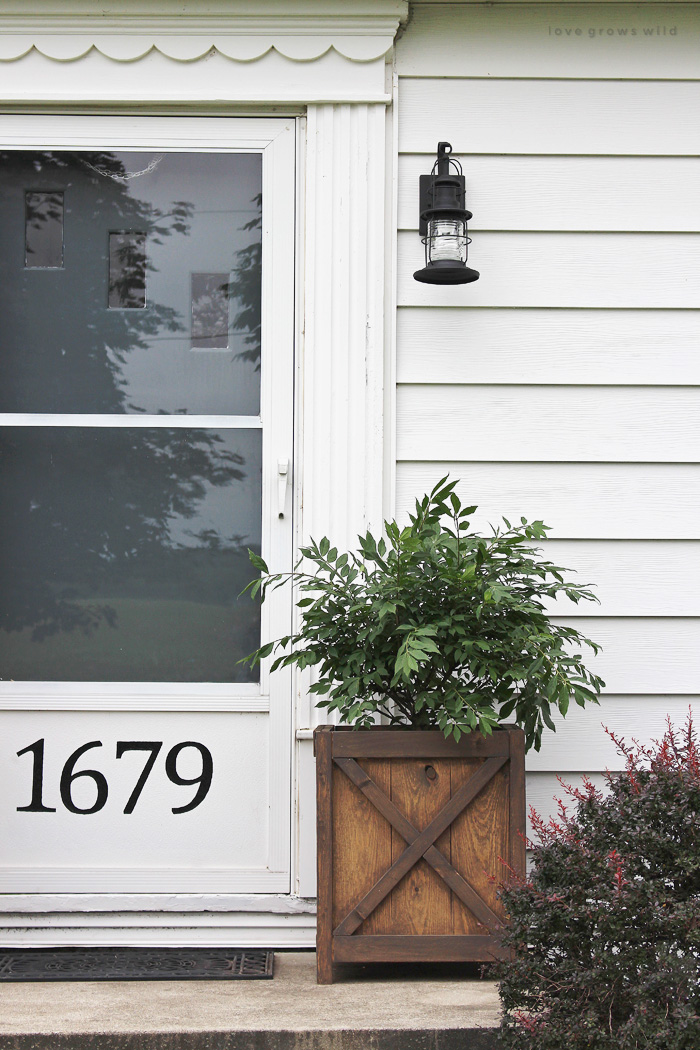 Get all the details of this charming front porch makeover featuring DIY wood planters and a lantern light fixture. | LoveGrowsWild.com