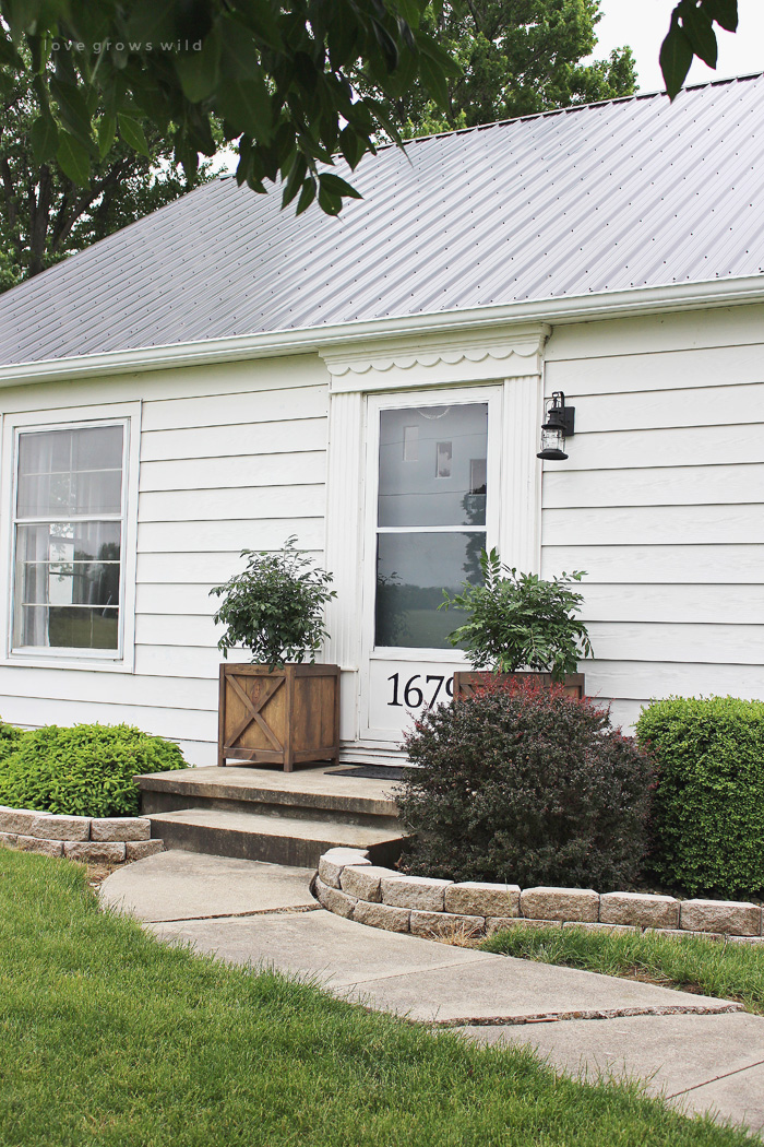 Get all the details of this charming front porch makeover featuring DIY wood planters and a lantern light fixture.   LoveGrowsWild.com