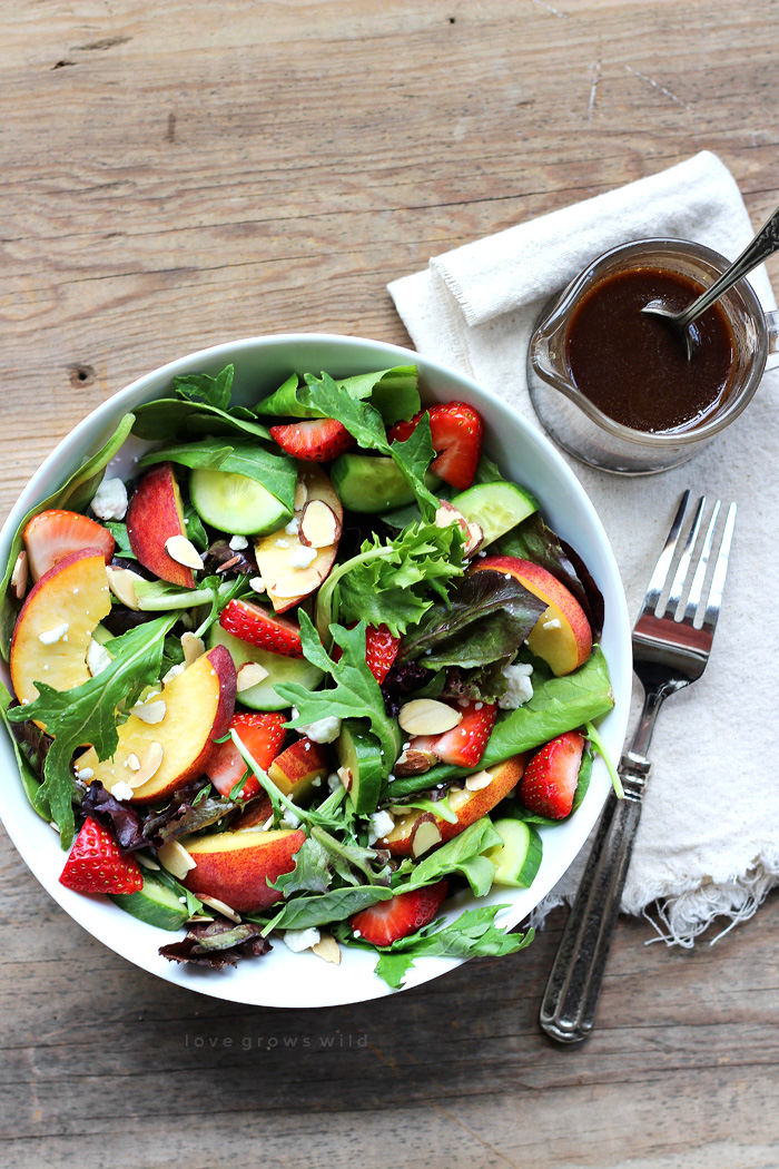 Try this fruity Strawberry Peach Salad for a fresh, fast, and healthy meal any time of day! Fresh greens topped with juicy peaches, ripe strawberries, cucumber, goat cheese, sliced almonds, and a yummy honey balsamic dressing.   LoveGrowsWild.com