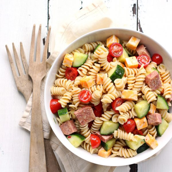 The perfect pasta salad recipe! Tender noodles tossed in a zesty Italian dressing with vegetables, meat, and cheese... great for a potluck or a light meal!   LoveGrowsWild.com