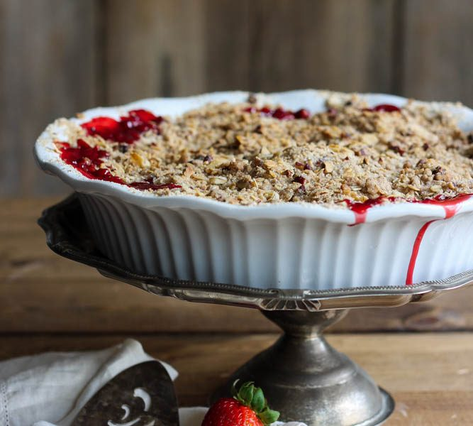 Delicious strawberry crisp made with fresh berries and a crunchy topping of oats and pecans. Serve warm out of the oven with a scoop of vanilla ice cream! | LoveGrowsWild.com