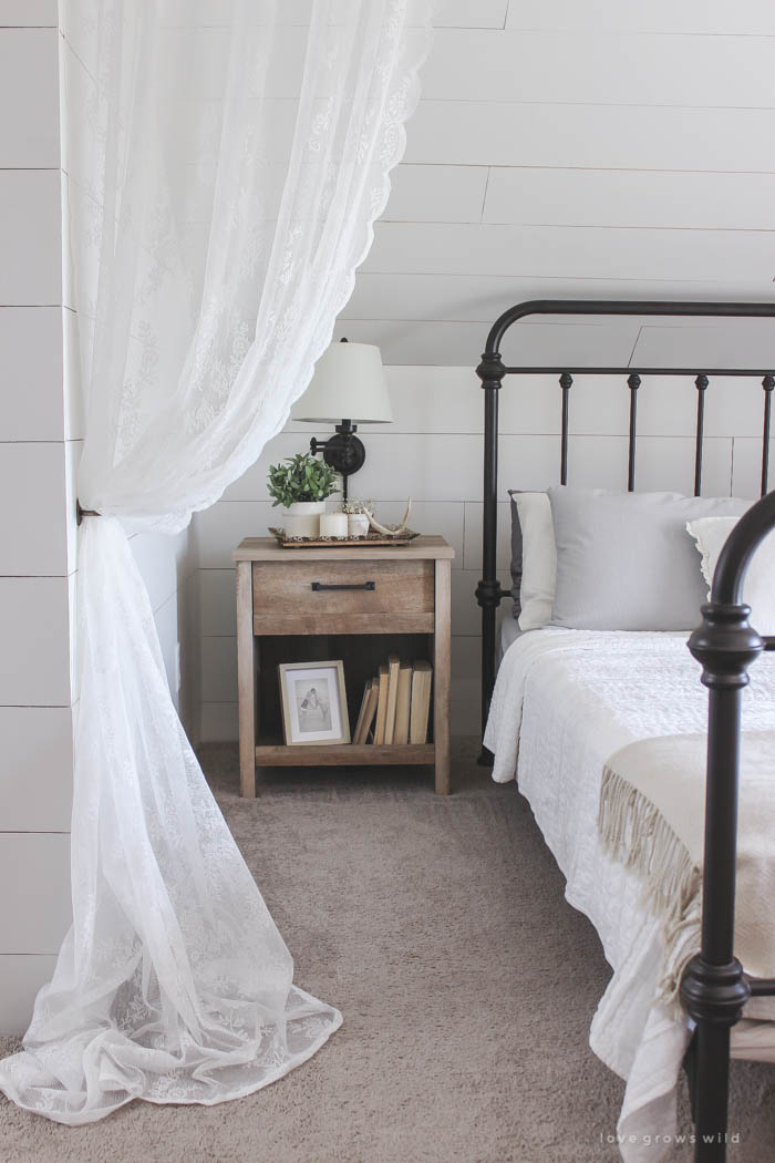 This cozy sleeping nook was created by adding a faux wood beam and lace curtains over the bed, and the results are amazing! See how to do this project in your home at LoveGrowsWild.com