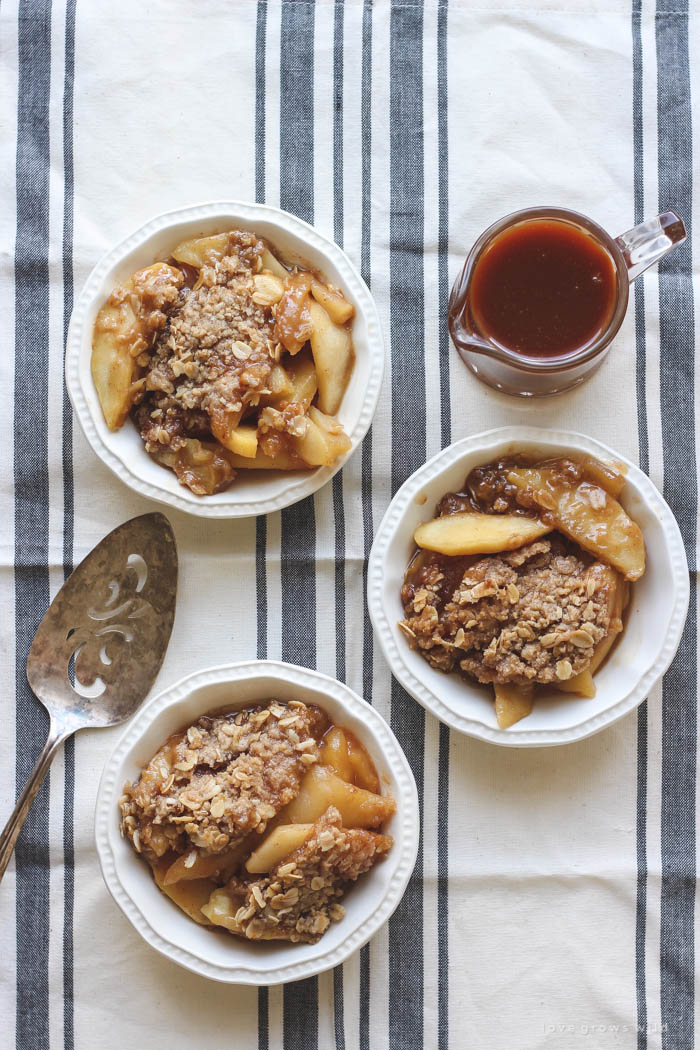 Warm salted caramel apple crisp topped with scoops of vanilla ice cream and more salted caramel drizzled over top... the perfect dessert! Get the recipe at LoveGrowsWild.com