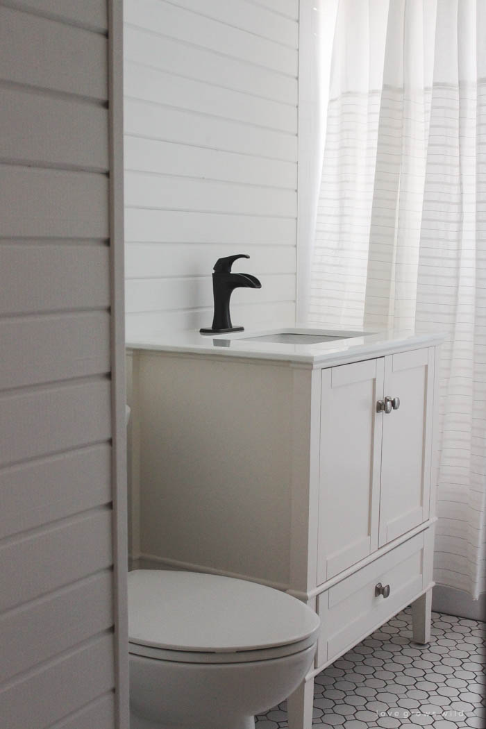 Follow along the big makeover of this beautiful farmhouse bathroom! In this post, Liz reveals her new planked walls, vanity, and closet! Click to see more photos at LoveGrowsWild.com