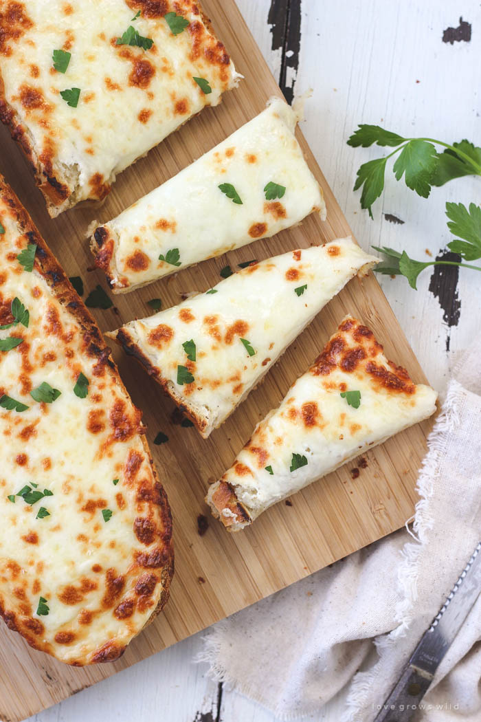 Delicious, extra cheesy garlic bread that is perfectly crusty on the outside and soft and tender on the inside! Find out the secret ingredient at LoveGrowsWild.com