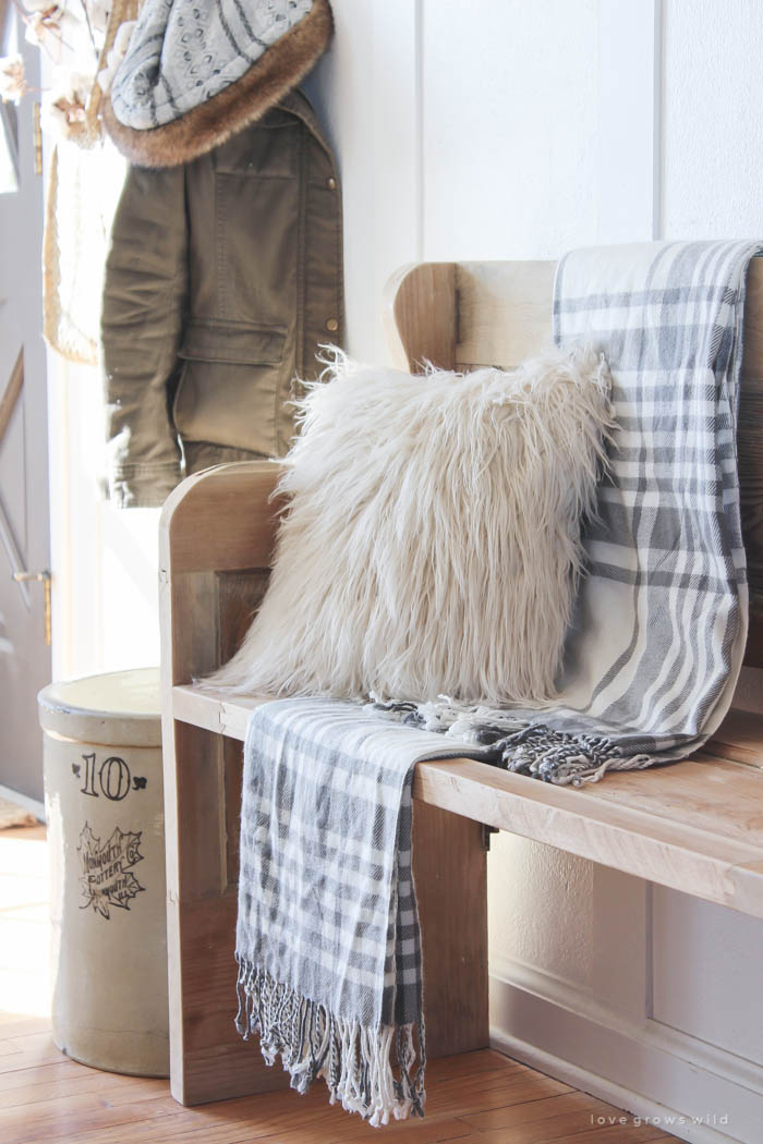 This simple farmhouse entryway is perfectly decorated for winter with large coat hooks, a rustic bench, and a place for snow-covered boots. See more photos at LoveGrowsWild.com