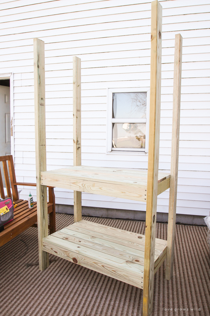 This stunning DIY potting bench is full of charm and perfect for a deck or patio! Use it to hold pots and gardening tools or as a beverage cart when entertaining guests! Full how-to at LoveGrowsWild.com
