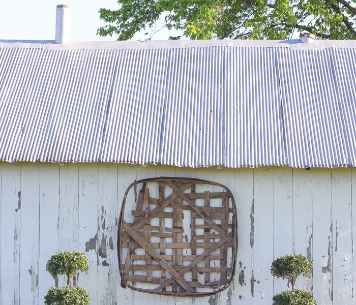 Outdoor decorating ideas including urn planters, an antique tobacco basket, boxwood topiaries and more! See more of this charming white barn at LoveGrowsWild.com