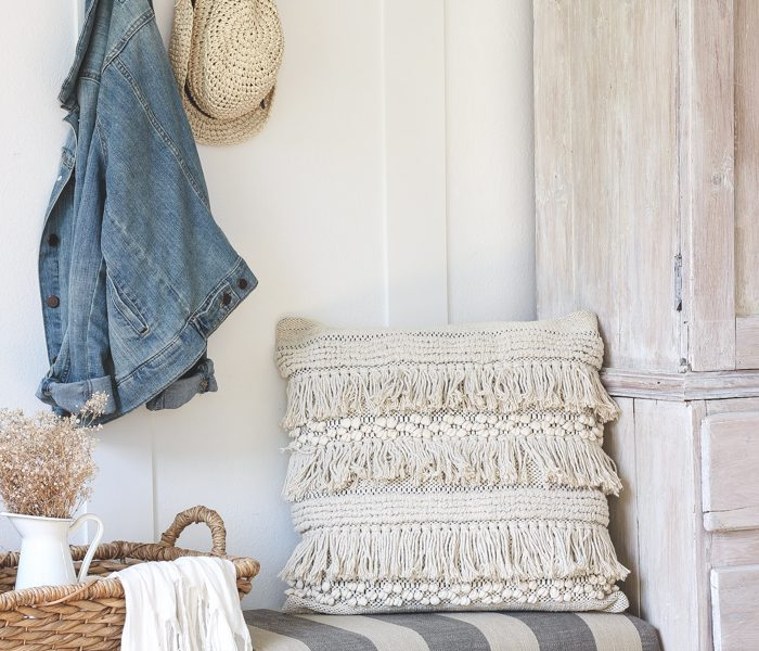This beautiful farmhouse entryway is the perfect mix of style and organization with a cozy bench, hooks for coat storage, and a basket for accessories.