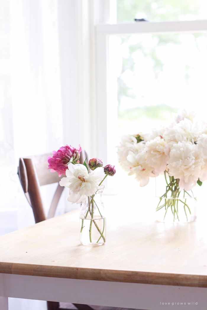 Freshly picked peonies decorate this beautiful farmhouse kitchen by Liz Fourez