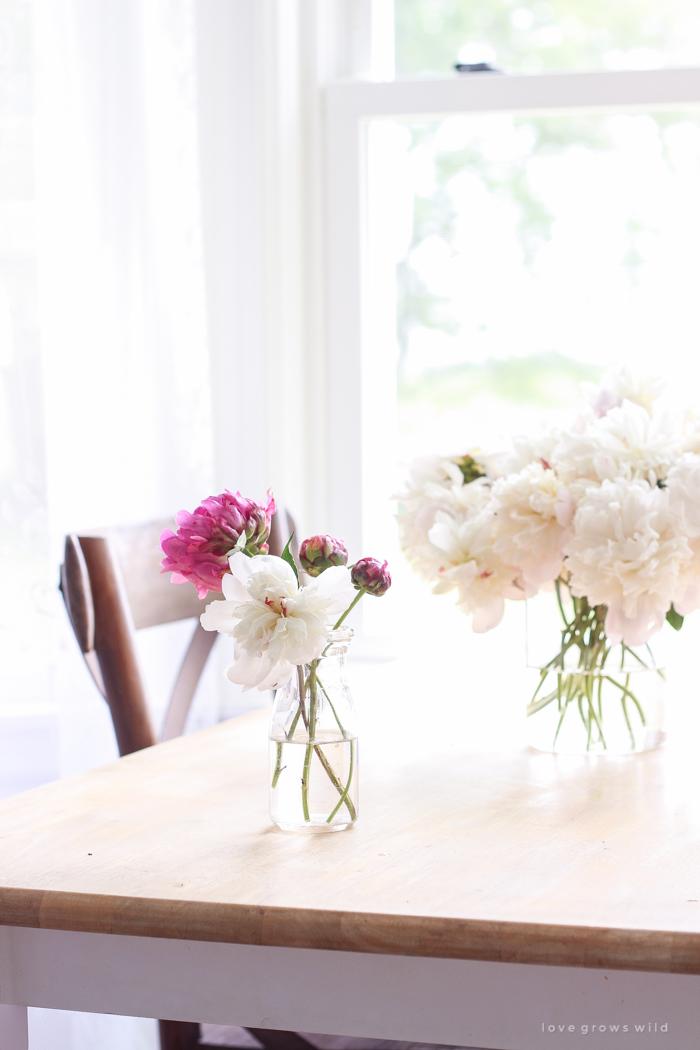 Freshly picked peonies decorate this beautiful farmhouse kitchen by Liz Fourez