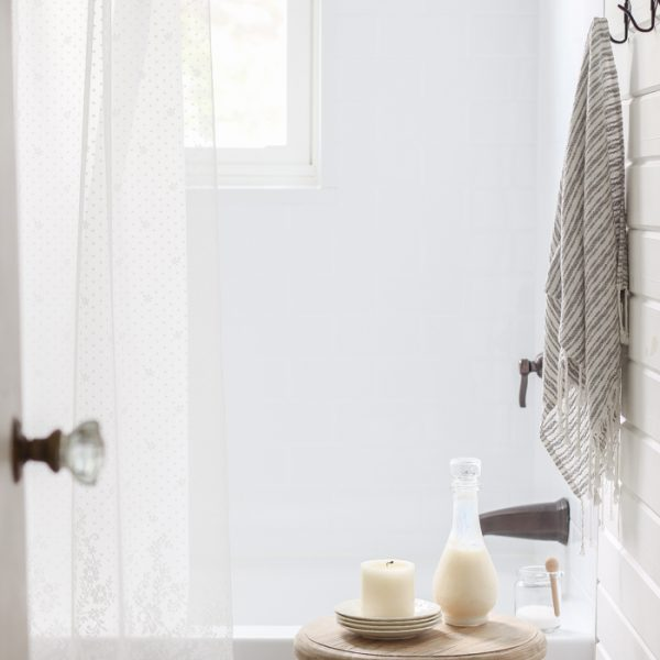 Touches of lace and other feminine fabrics soften this beautiful farmhouse for easy summer style.