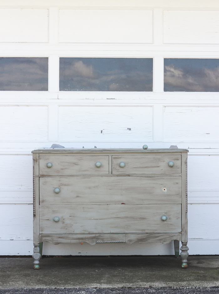 An old dresser gets a makeover with soft blue paint and a delicate hand painted design