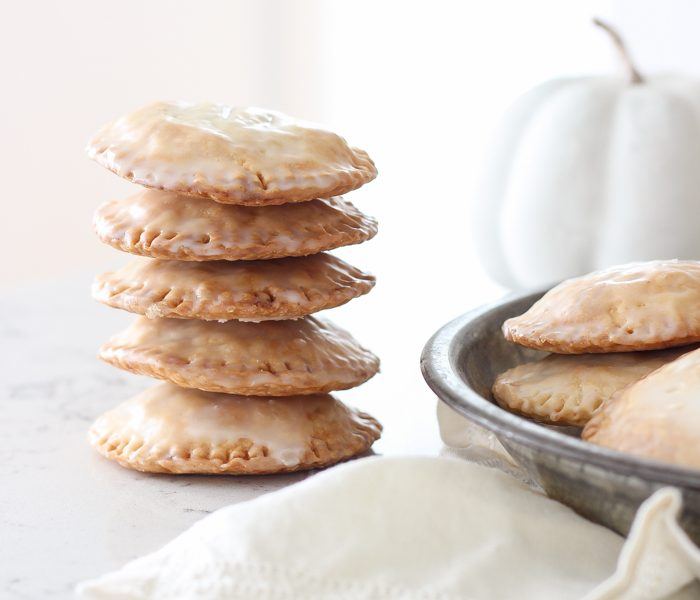 Maple Glazed Pumpkin Hand Pies - Adorable mini pies with cinnamon infused pumpkin filling wrapped in flaky pie crust and topped with a sweet maple glaze!