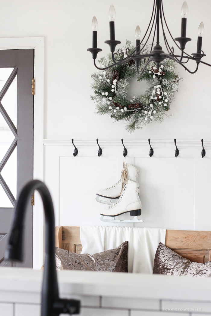 A simple winter white entryway decorated for the holidays in a beautiful farmhouse