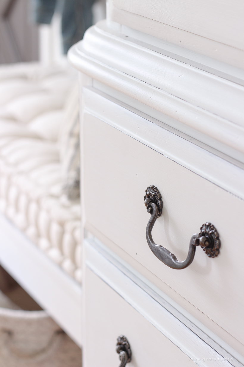 A dark and dated armoire gets a makeover with creamy white paint and beautifully distressed details. Find out how to easily antique furniture with this tutorial!