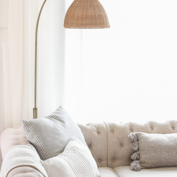 A gorgeous antique brass and rattan floor lamp is the perfect accessory in this neutral living room. See more details in this blog post!