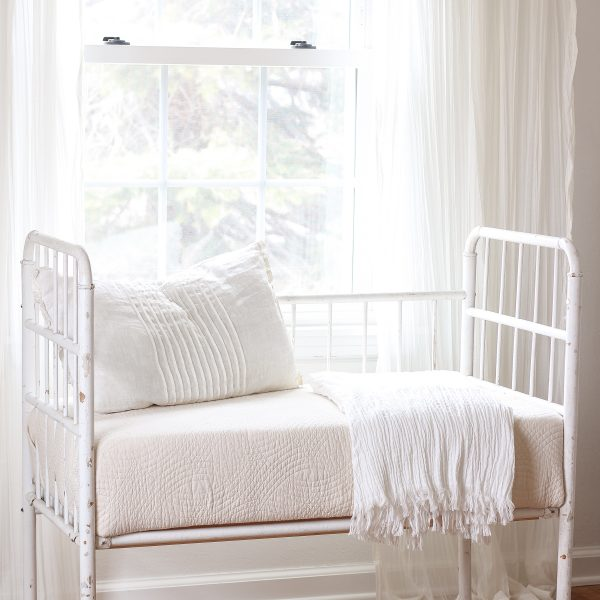 Home and lifestyle blogger Liz Fourez turns a wooden antique crib into an adorable bench with a quilted cushion.