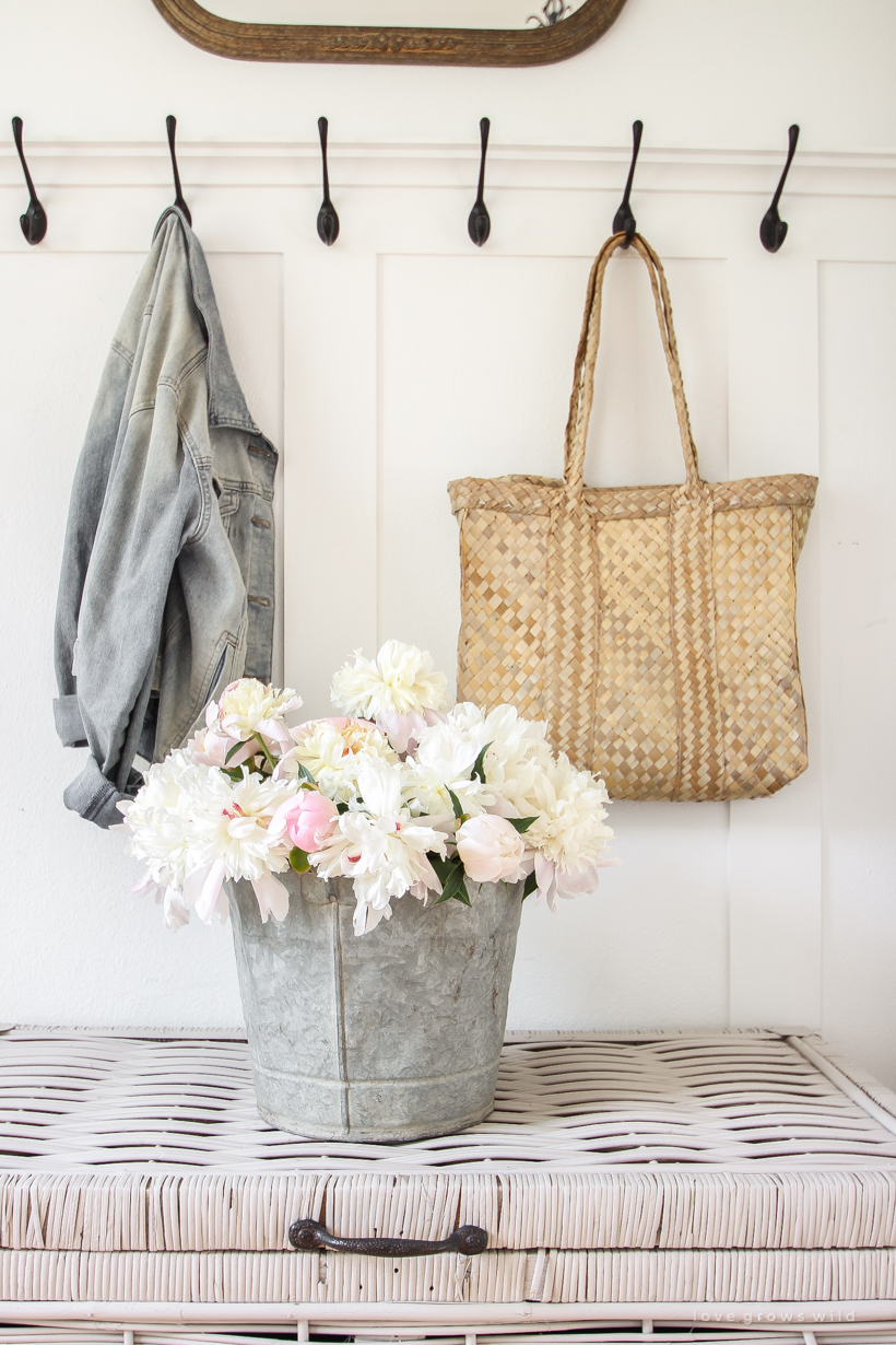 Bucket of peonies styled in an entryway