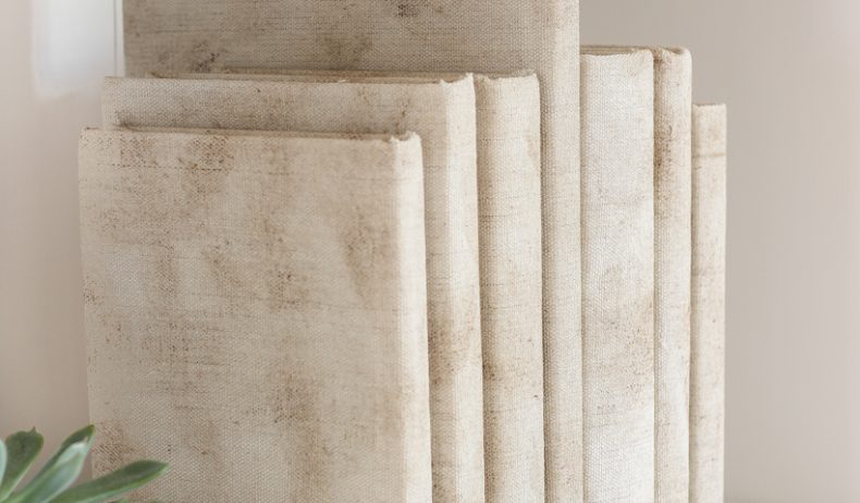 How to cover books in a beautifully distressed canvas fabric to use for styling shelves and tables.