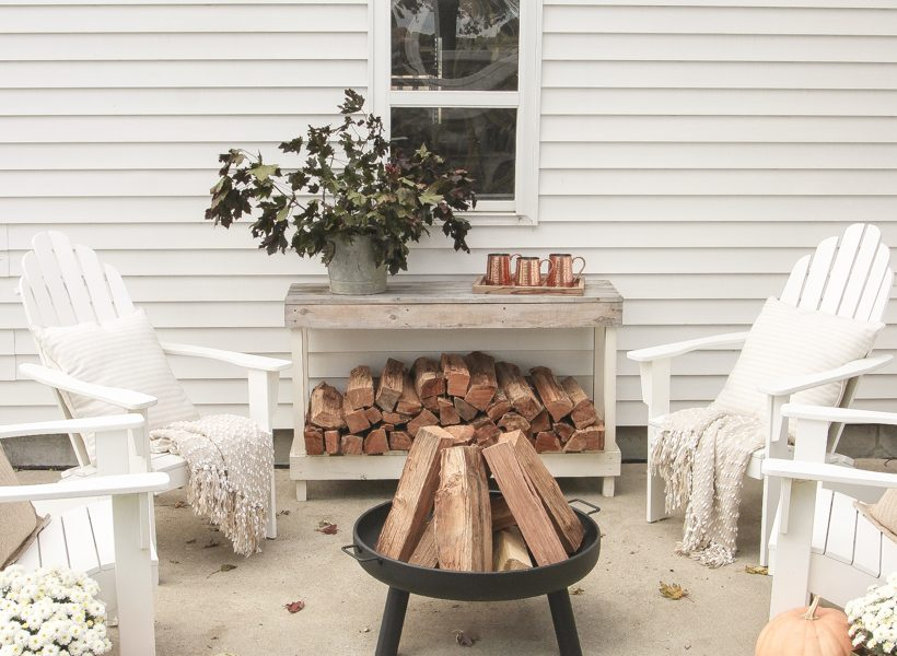 A cozy outdoor space to relax in with a simple fire pit, white adirondack chairs, and beautiful fall decor. See more details at lovegrowswild.com